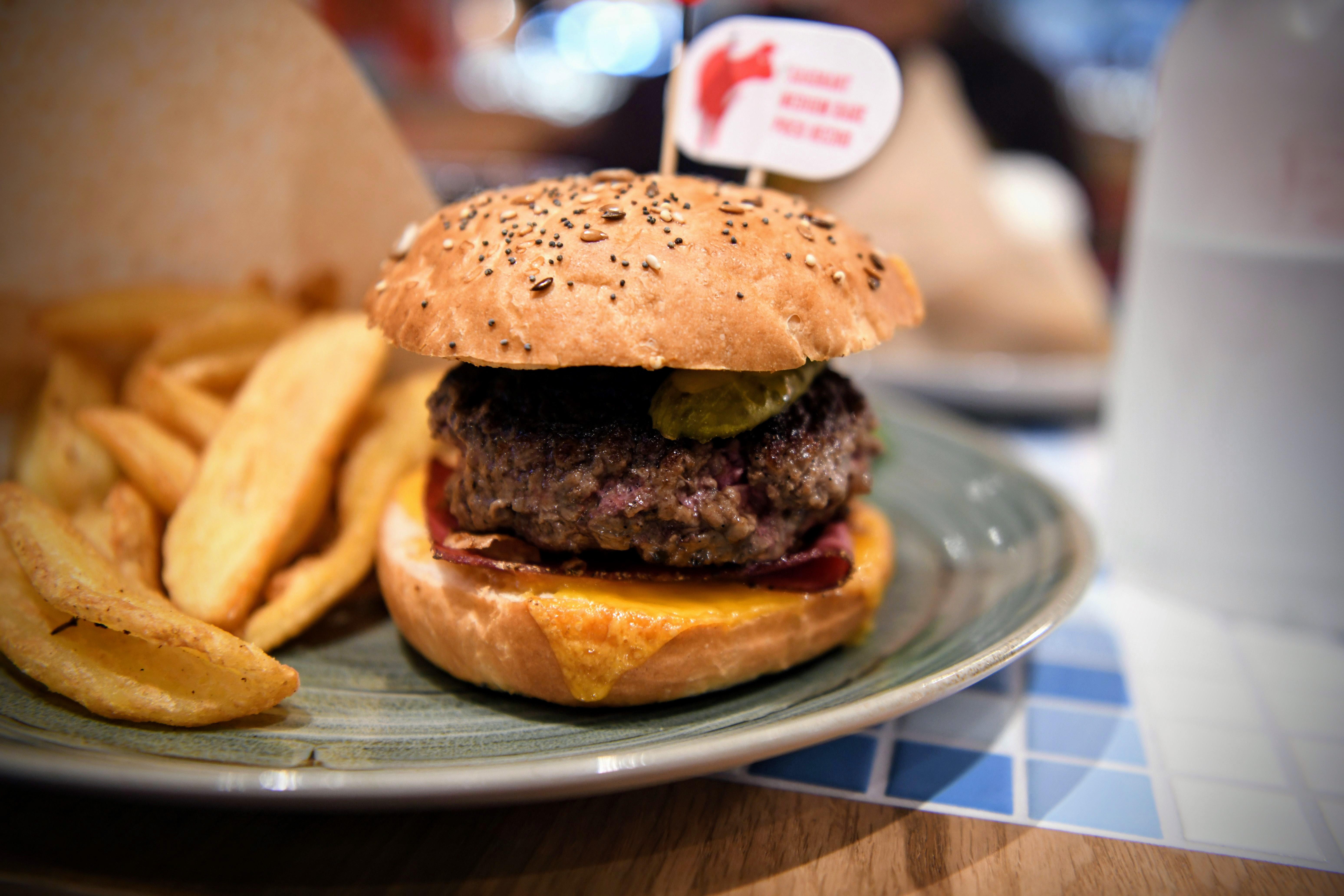 Pain maison, steak haché, sauce ketchup, lard grillé, tomate, cornichon aigre doux, cheddar rouge
